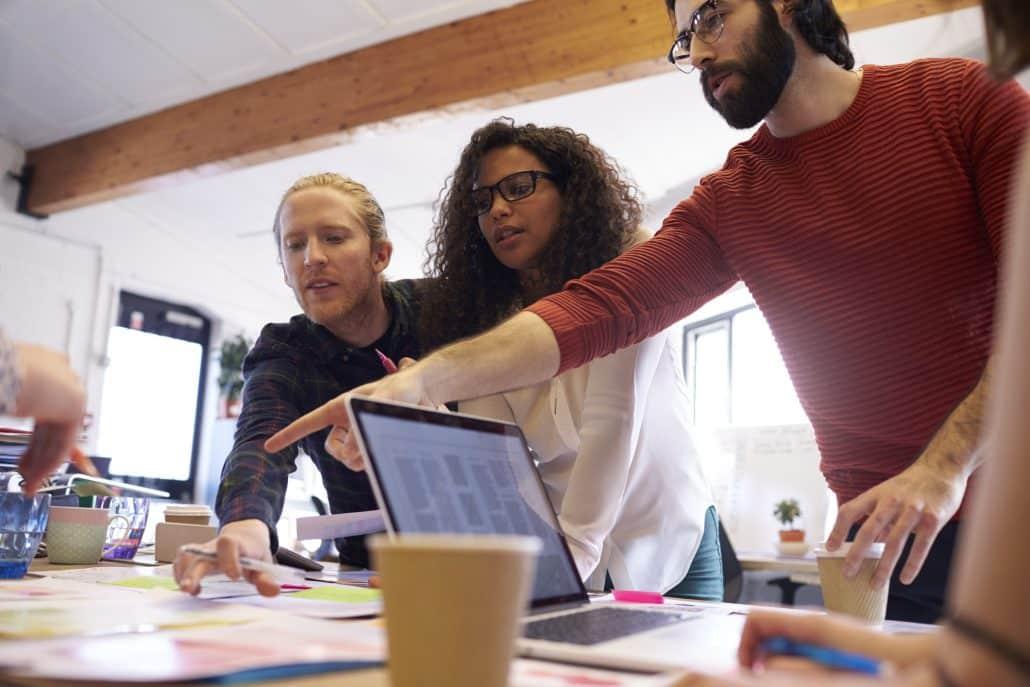 Ein Team arbeitet zusammen an einem großen Tisch, es werden Skizzen umhergeschoben.